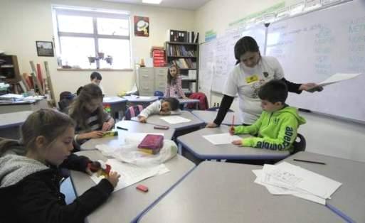 A professora Alessandra Lima ajuda o estudante Nicholas Almeida em aula de português do Sturgis Charter Public School, no Cabo Cod.