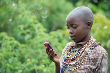 Uma menina do povo massai a ler texto em seu telemóvel no Quénia: ferramenta importante para leitura onde é difícil o acesso a livros.